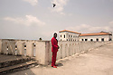 """Ghana - El Mina - A local priest stands on the rooftop of the castle. A UNESCO World Heritage Site, the Castle of Elmina was built by the Portuguese in 1487 and was the first """"slave fort"""" to be erected along the West Africa coast. Today, the Elmina coast is threatened by coastal erosion, mostly due to uncontrolled sand mining which has permanently damaged the town's beaches."""