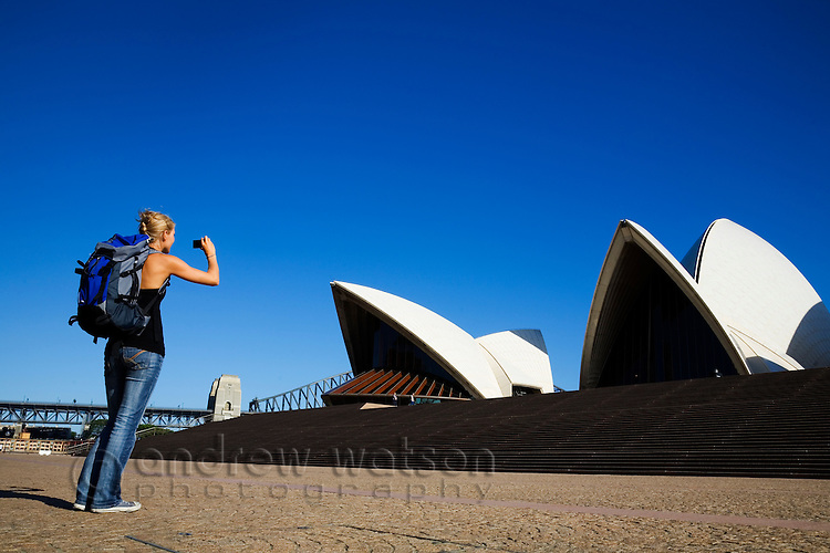 A backpacker photographs the Sydney Opera House.  Sydney, New South Wales, AUSTRALIA.