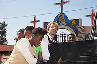 "Ethiopia. Oromiya Region. Walliso. The Christian Cross at a church's entrance. Colorful paintings with the Virgin Mary. Marc Vella is a french musician and a nomadic pianist. Over the last 25 years he has travelled with his Grand Piano in around forty countries to celebrate humanity. Creator of ""La Caravane amoureuse"" (The Caravan of Love) he takes people with him to say ""I love you"" to others and ""lovingly conquered"" their hearts and souls. Marc Vella and a group of ethiopian young men play an improvised duet-playing - one piano and four hands. Mary, also known as St Mary the Virgin, the Blessed Virgin Mary, Saint Mary, Mary the Mother of God, or the Virgin Mary was the mother of Jesus. The Christian Cross, seen as a representation of the instrument of the crucifixion of Jesus, is the best-known symbol of Christianity. 16.11.15 © 2015 Didier Ruef"