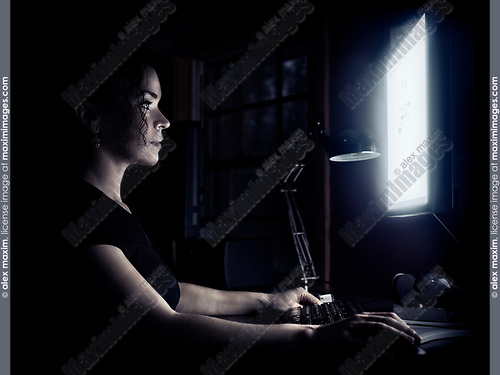 Young woman sitting at a desk at home using a computer with her face illuminated by the light of the monitor screen