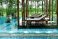 The square 25-meter swimming pool at The Sarojin luxury resort hotel in Khao Lak, Thailand, has a jacuzzi lounge area and three drape shaded pool island pavilions. Designed in a contemporary Asian style, The Sarojin is located about an hour north of Phuket along the Andaman Coast..