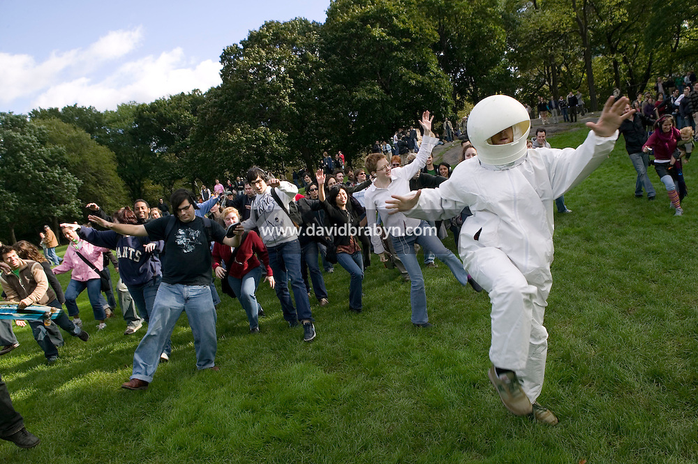 "16 October 2005 - New York City, NY - People following instructions playing on their handheld digital music players space-walk behind Flynn Barrison (astronaut costume) across Central Park, New York City, USA, 16 October 2005, during a so-called ""MP3 Experiment"" organized by Improv Everywhere, a group of young artists which seek to organize bizarre, anonymous happenings and pranks."