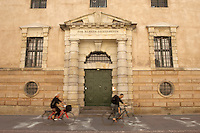 Bike riders in front of CF Hansen's Arresthus (a jailhouse, built between 1803 and 1816) designed by the famous danish neo-classical architect Christian Frederik Hansen (1756-1845). &quot;For almeen sikkerheden&quot; can be translated as &quot;for the security of the public&quot;. Slutterigade, Copenhagen, Denmark.<br /> August 2008.<br /> Only for editorial use.