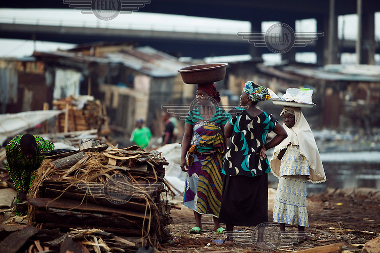 Women selling food carry it in bowls on their heads in the Ebute Metta neighbourhood, home to Lagos's timber milling industry.