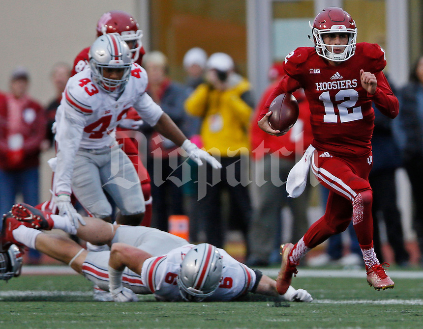 Indiana Hoosiers quarterback Zander Diamont (12) escapes Ohio State Buckeyes defensive end Sam Hubbard (6) and Ohio State Buckeyes linebacker Darron Lee (43) to scores a touchdown in the second half the Ohio State Buckeyes against  the Indiana Hoosier at Memorial Stadium in Bloomington Indiana Oct. 3, 2015.(Dispatch photo by Eric Albrecht)