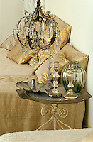 Detail of a bedside table with candlesticks and a French glass chandelier