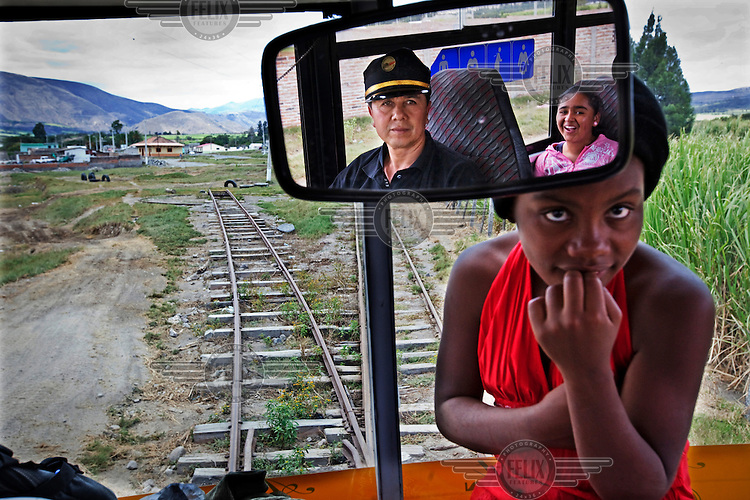 A girl sits next to the conductor, reflected in a mirror, on the tourist train in Ibarra. An old bus was converted and fitted with railway wheels as part of the town's rehabilitation project.