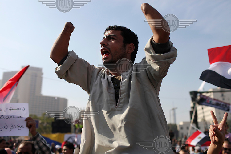 A man, with a double wrist disarticulation (amputation), shouts during a demonstration in Tahrir Square against President Mohamed Mursi (Morsi) and the Islamist-led assembly. Thousands of people gathered to protest after the assembly pushed through approval of a new constitution that was itself a bid to end the crisis that blew up in response to Morsi's perceived overly-extended powers.