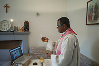 "Switzerland. Canton Ticino. Grancia. Reverend Father Gerald Chukwudi Ani celebrates the Sunday mass at home and transmits it live on YouTube. Don Gerald Chukwudi Ani, originally from Nigeria, is a catholic priest from the Diocese of Lugano. Sacramental bread (Latin: hostia, Italian: ostia), sometimes called altar bread, Communion bread, the Lamb or simply the host, is the bread or wafer used in the Christian ritual of the Eucharist. Eastern and Western traditions both require that it be made from wheat. Transubstantiation is, according to the teachings of the Roman Catholic Church, the change of substance or essence by which the bread and wine offered in the sacrifice of the sacrament of the Eucharist during the Mass, become, in reality, the body and blood of Jesus Christ. Due to the spread of the coronavirus , the Federal Council has categorised the situation in the country as ""extraordinary"". It has issued a recommendation to all citizens to stay at home, especially the sick and the elderly. From March 16 the government ramped up its response to the widening pandemic, ordering the closure of bars, restaurants, sports facilities and cultural spaces. Celebrating masses is prohibit in order to avoid people meeting together. On the wall, a wooden crucifix with Jesus Christ on the cross. On the shelf (Left to right) : A swiss clock. A picture taken at a baptism ceremony in Italy. A statue of Our Lady of Fátima (Our Lady of the Holy Rosary of Fátima). A wooden model of a catholic church. A traditional Igbo mask (Igbo is an ethnic tribe of southeastern Nigeria). On the wall (R) a painting about the Holy Trinity. The Christian doctrine of the Trinity holds that God is three consubstantial persons or hypostases—the Father, the Son (Jesus Christ), and the Holy Spirit—as ""one God in three Divine Persons"". The three Persons are distinct, yet are one ""substance, essence or nature"". YouTube is an American online video-sharing platform. Grancia is a municipality in the"
