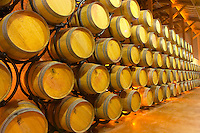 The barrel ageing cellar. The oak barriques are stacked in a steel construction with rollers that makes it possible to turn the barrels around to stir the lees instead of doing batonnage (stirring the lees with a stick) Chateau Thieuley La Sauve Majeure Entre-deux-Mers Bordeaux Gironde Aquitaine France