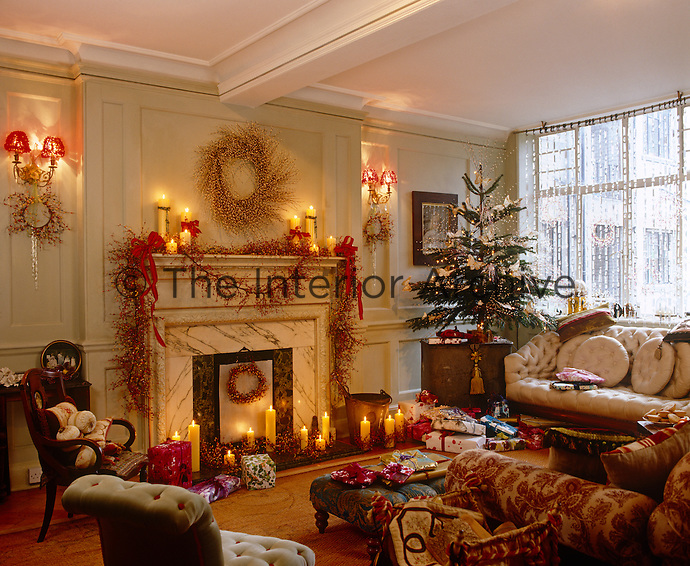 A cheerful Christmas scene has been created in this candlelit living room with piles of presents, decorations and a Christmas tree