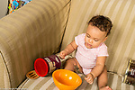 Infant development 9 month old baby girl playing with metal spoon and bowl