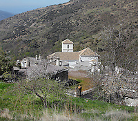 Bubion, seen from the hillside, with mudejar style Church of La Virgen del Rosari, 16th century, gorge of the Poqueira river, Alpujarra, Andalucia, Southern Spain. Moorish influence is seen in the distinctive cubic architecture of the Sierra Nevada's Alpujarra region, reminiscent of Berber architecture in Morocco's Atlas Mountains. Photograph by Manuel Cohen.
