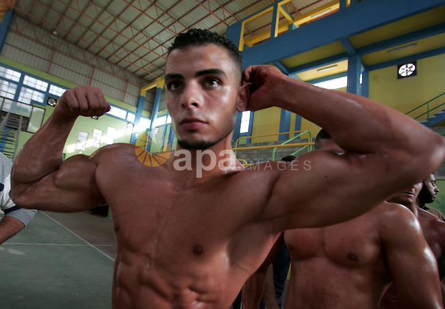 Palestinian men pose as the compete in the Khadamat Rafah club, in the southern Gaza Strip, on July 23, 2010. Many of the men use women's cosmetics, mud, or paint to enhance their muscles, with some 39 men from around the Gaza Strip took part in the territory's bodybuilding championship. Participants say the Israeli-Egyptian blockade makes it harder for them to pump up and prevents them from participating in championships outside of the impoverished territory. Photo by Khaled Khaled