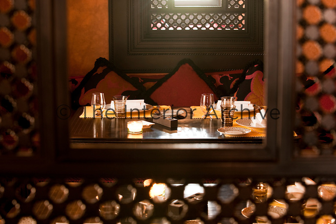 The laid table is reflected in the mirror in a warmly decorated alcove at Le Restaurant Marocain