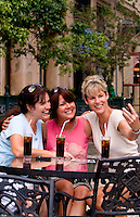 Tourist girl friends relax with drinks and take Iphone photos and have fun in Old Havana in Habana Cuba