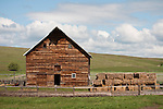 Weathered wooden barn and hay bale stack, rural Wallowa County, Ore.