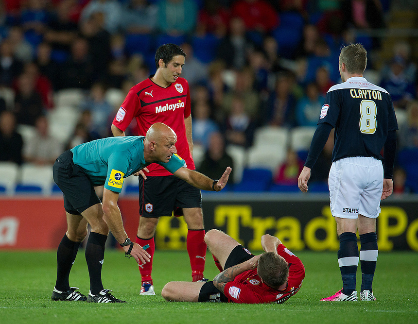 Referee Roger East calls for a trainer to attend to Cardiff City's Aron Gunnarsson ..Football - npower Football League Championship - Cardiff City v Huddersfield Town - Friday 17th August 2012 - Cardiff City Stadium - Cardiff..