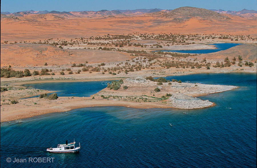 """Plus grand lac artificiel du monde, le lac Nasser s'étire sur plus de 500 km au sud du barrage d'Assouan et sa profondeur dépasse parfois 180 m. La construction du barrage a mis sous l'eau toute une région  d'Assouan à Abou Simbel. Près de 800 000 Nubiens présents avant les temps pharaoniques ont du quitter la terre de leurs ancêtres...Shared between Egypt and Sudan, the ancient Nubia has been drowned in the waters of Lake Nasser. It's now possible to navigate in this strange aquatic desert, in search of peace, nature and """"ka"""", the soul of the ancient Egyptians. Nasser Lake.  Egypt."""
