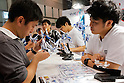 Macross fans test action figures at the 56th All Japan Model & Hobby Show in Tokyo Big Sight on September 25, 2016. The exhibition introduced hobby goods such as plastic models, action figures, drones, and airsoft guns. (Photo by Rodrigo Reyes Marin/AFLO)