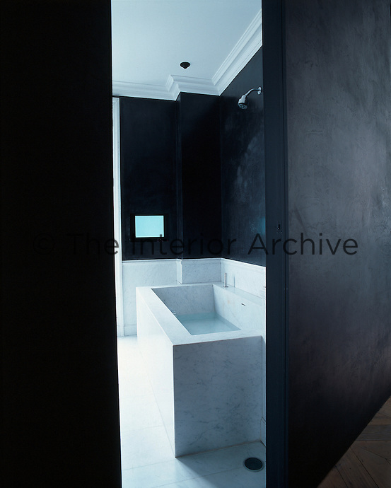 In the white Carrara marble bathroom the black walls are covered in a polished plaster finish known as marmorino