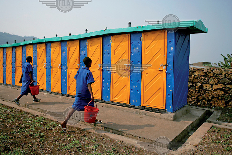 Two girls with pails walk towards latrines at Umubano II Primary School in the town of Gisenyi in Western Province. More than half of the school's 800 students are girls.