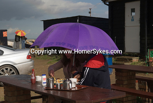 Eating fish and chips in the rain, Bank Holiday Monday Dunwich Suffolk, England 2006,