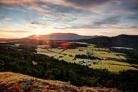 The sun rises over the Mount Constitution and the Crow Valley, viewed from Ship Peak on Turtleback Mountain, Orcas Island, Washington, USA