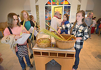 NWA Democrat-Gazette/BEN GOFF -- 03/29/15 Christie Krumwiede (from left) and son Grant Hall, 15, of Springdale and Phyllis Hunter and daughter Rebecca Hunter, 16, of Fayetteville return their palm fronds after a Palm Sunday service at St. Thomas Episcopal Church in Springdale on Sunday Mar. 29, 2015.