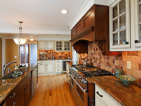 Arts & Crafts style kitchen with painted cabinets, dark walnut cabinets, granite coounters, stainless professional stove, sink with faucet and wood plank floor.