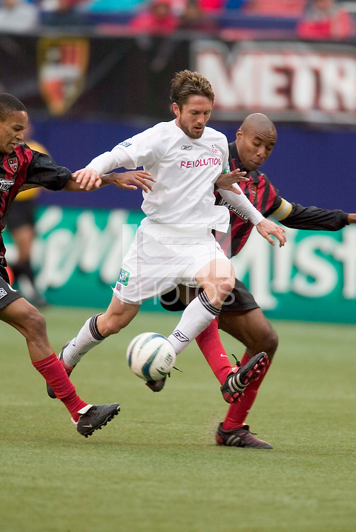 New England Revolution's Joe-Max Moore attempts to split the defense of the MetroStars' Ricardo Clark and  Eddie Pope. The New England Revolution played the NY/NJ MetroStars to a 1 to 1 tie at Giant's Stadium, East Rutherford, NJ, on April 24, 2004.
