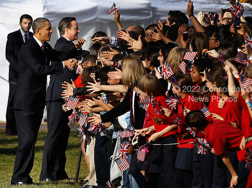 U.S. President Barack Obama (L) and British Prime Minister David Cameron greet guests and school children during an official arrival ceremony on the South Lawn of the White House March 14, 2012 in Washington, DC. Cameron was on a three-day visit in the U.S. and he was expected to have talks with Obama on the situations in Afghanistan, Syria and Iran. .Credit: Chip Somodevilla / Pool via CNP