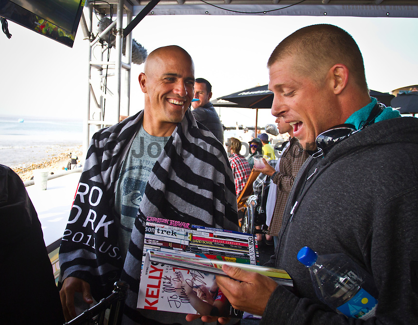 """LOWER TRESTLES, California/USA (Wednesday, September 21, 2011) Mick Fanning (AUS) gets an autograph from Kelly Slater (USA).  - Kelly Slater (USA), 39, has won his fifth Hurley Pro at Trestles title, defeating Owen Wright (AUS), 21, in a hard-fought Final that saw the iconic Floridian overtake the young Australian in a last-minute exchange with a final score of 17.50 to 16.74...Slater and Wright's third consecutive Final bout marks a first in ASP history, as no two competitors have faced off in three successive ASP Dream Tour Finals - a noteworthy statistic in sparking this new rivalry in the battle for the ASP World Title...Slater roared to life on the Final day, unloading the highest heat-total of competition, 18.40 out of 20 in the Semifinals, and maintained his lethal form throughout the day's entirety with a consistent display of new-school airs and patented carves to clinch his unprecedented 48th elite ASP World Tour victory and third of the season...""""Owen (Wright) is tough and he's been surfing great,"""" Slater said. """"There really are no weak points to his surfing and he's going to be a standout in every spot. A lot of the guys tried to get him this week and I got lucky in that last exchange. I was taking the first wave of the set under his priority and once I got priority I wanted to wait. It almost looked like there wasn't a wave after Owen's. It's been fun surfing against Owen and surfing Lowers. It's been a great week and thanks everyone for the crazy support, it's been wonderful.""""..Wright, current No. 2 on the ASP World Title rankings, has continued to build momentum throughout his sophomore year amongst the ASP Top 34 and dispatched of a rampaging Mick Fanning (AUS), 30, and rookie prodigy Julian Wilson (AUS), 22, en route to his rematch against Slater, but was unable to solidify the victory over the veteran in the Final.  Photo: joliphotos.com"""