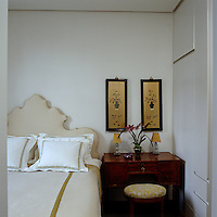 A pair of Chinese prints hangs above the small wooden dressing table in the corner of the guest bedroom