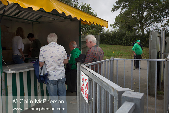 Home fans paying at the turnstiles as Guernsey take on Corinthian-Casuals in a Isthmian League Division One South match at Footes Lane. Formed in 2011, Guernsey FC are a community club located in St. Peter Port on the island of Guernsey and were promoted to the Isthmian League Division One South in 2013. The visitors from Kingston upon Thames won the fixture by 1-0, watched by a crowd of 614 spectators.