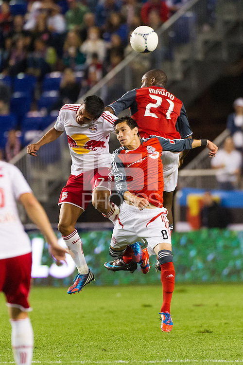 Tim Cahill (17) of the New York Red Bulls goes up for a header with Eric Avila (8) and Aaron Maund (21) of Toronto FC. The New York Red Bulls defeated Toronto FC 4-1 during a Major League Soccer (MLS) match at Red Bull Arena in Harrison, NJ, on September 29, 2012.