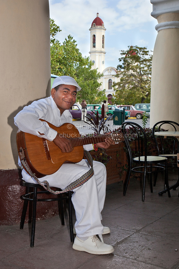 Cuba, Cienfuegos.  Afro-Cuban Guitar Player outside a Cafe.  Church of La Purisima Concepcion in Background.