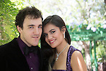 Mixed race young woman and Caucasian young man dressed in formal purple attire for prom