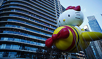 USA, New York, Nov 28, 2013. People try to watch the Hello Kitty balloon while it takes part in the 87th Macy's Thanksgiving Day Parade in New York City. Photo by VIEWpress/Eduardo Munoz Alvarez