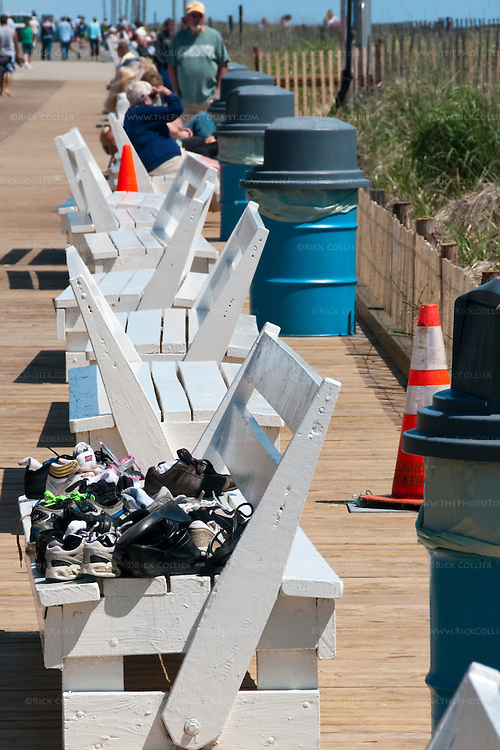 A group of kids has piled their shoes on a freshly painted bench so they could go walk on the beach on one of the first warm days at Rehoboth Beach, Delaware, USA.