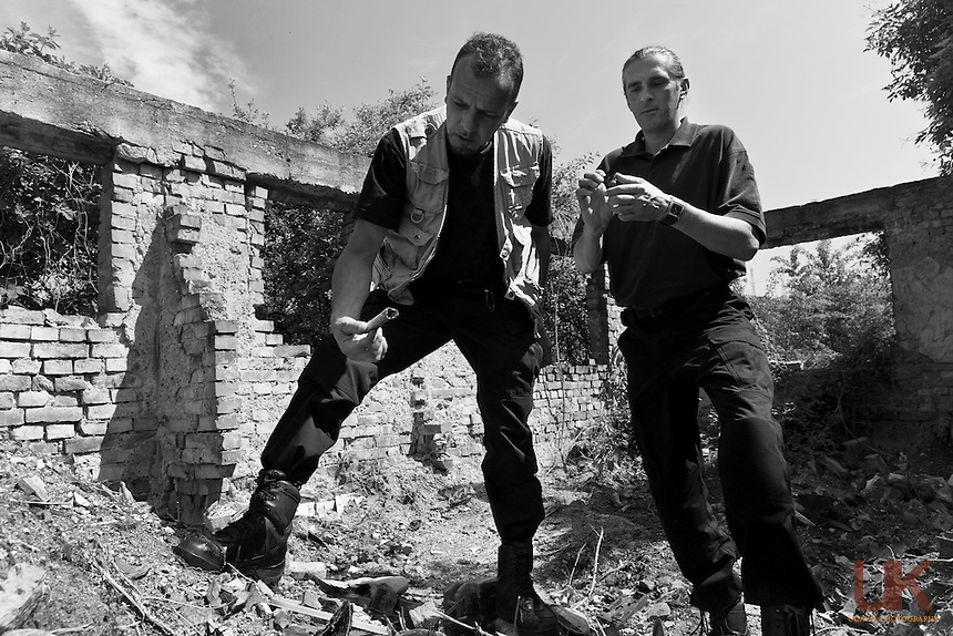 Suvad Halilovic (left) and Samir Sabanija(right) show bones and remains from a house in Rogatica, Bosnia where 8 people were burnt alive.