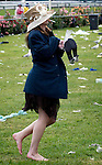Melbourne Cup at Flemington. Cigarette in mouth, shoes in hand and the champagne glass is empty - the end of the party for another year.