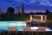 The outdoor swimming pool and pergola are lit up at night