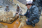 Freddy Llanos, a professor of mining engineering at Tomas Frias University, samples water quality outside the Kumurana Mine near Caiza D, Bolivia. The mine, which is closed, produces highly toxic acid runoff that negatively impacts the farms and lives of people living downstream. Llanos is working with an international coalition that is working with local miners and farmers to clean up the mine's runoff. Helping Llanos is Policarpio Montesinos, a local miner.