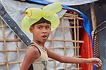 A boy wears a balloon hat as he walks through the sprawling Kutupalong Refugee Camp near Cox's Bazar, Bangladesh. More than 600,000 Rohingya refugees have fled government-sanctioned violence in Myanmar for safety in this and other camps in Bangladesh.