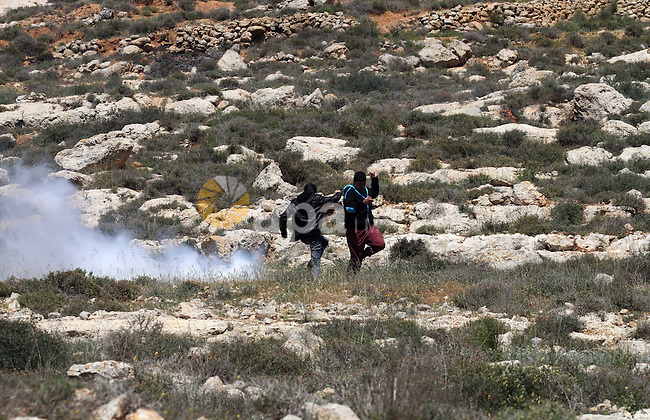 Palestinian protesters run for cover from tear gas fired by Israeli security forces during clashes following a demonstration against Jewish settlements in the West Bank village of Qaryout near Nablus on April 01, 2016. Photo by Nedal Eshtayah