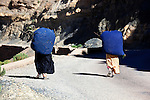 Two women in the mountains carying grass on their back, Morocco.