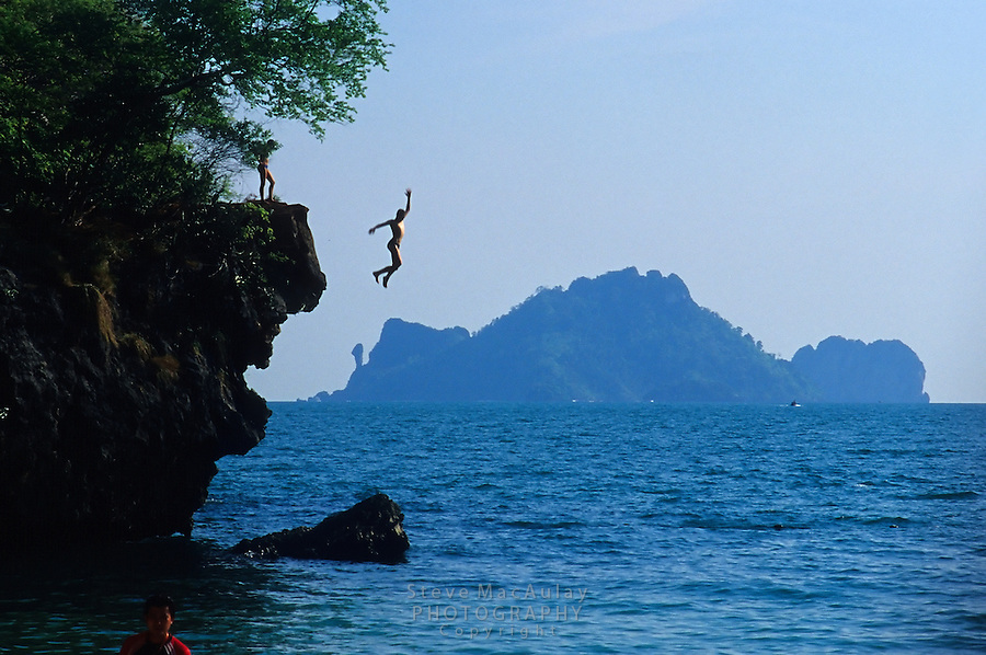 Young boy leaping into water from cliff, Railay Rei Lei Beach, Thailand