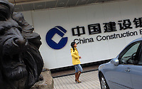People pass the China Construction Bank in Guangzhou, China. The Bank recently bought the Bank of America for 9.7 billion US$ in cash.                                                                                                                    .