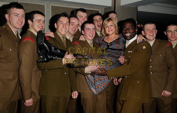 BIRGIT BEER & GUESTS .Attends 'Mad Hatters Tea Party' event organised by London Taxi Drivers Fund for Underprivileged Children at the Grosvenor House Hotel, Park Lane, London, England, UK..January 31st 2010..half full length army uniform lifted carried lifting boots black dress brown print orange pattern green red khaki soldiers .CAP/CAN.©Can Nguyen/Capital Pictures